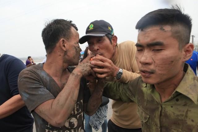 Mọi người cùng nhau chạm tay thậm chí hôn quả phết dù đầy bùn đất để lấy may.