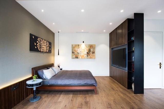 Phòng ngủ dùng nhiều mảng gỗ tối nhưng không có cảm giác nặng nề nhờ sự kết hợp của các mảng tường sáng, nội thất hiện đại cùng các bức tranh nhã nhặn.