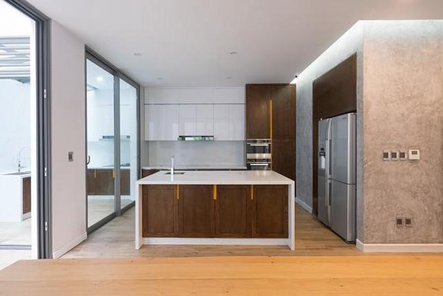 Đảo nấu cùng tủ bếp đều được sơn màu trắng tạo cảm giác sạch sẽ và rộng thoáng hơn.