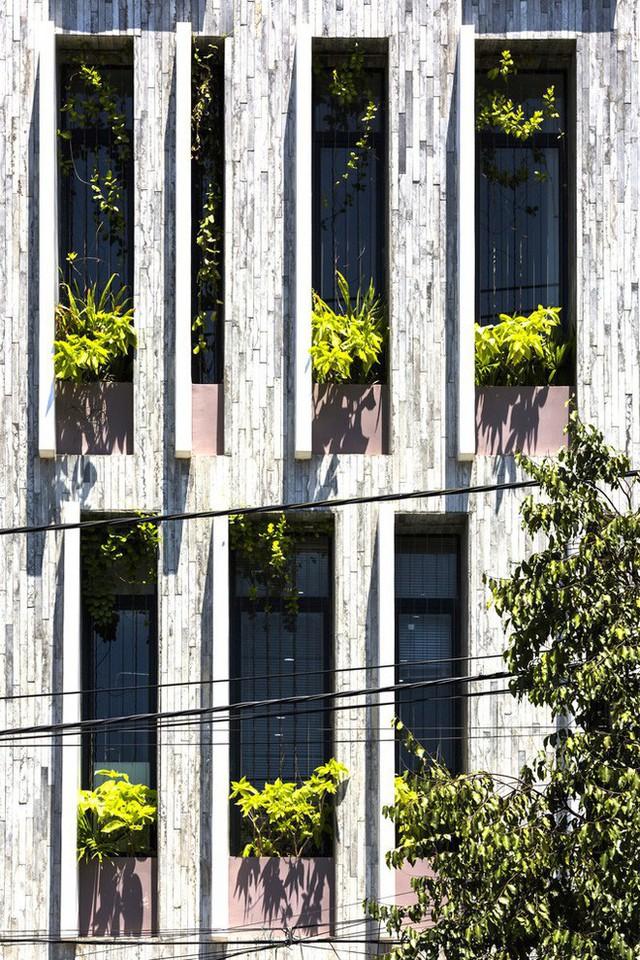 Chất liệu bê tông đúc, kính và cây xanh mang đến cho mặt tiền ngôi nhà sự thu hút.