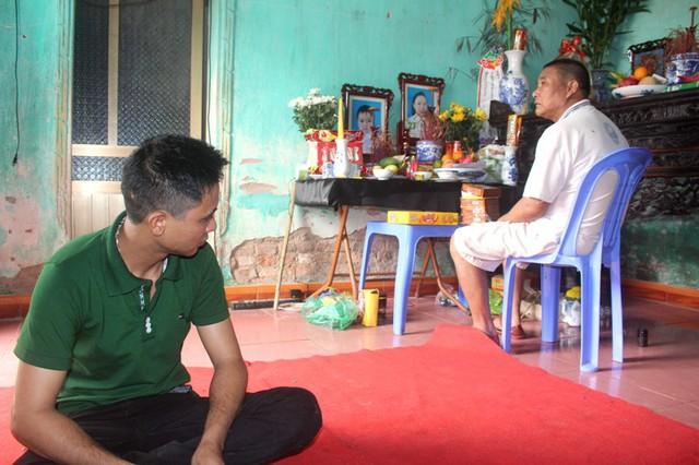 Ông Hà Văn Muộn (bố anh Linh - ngồi ghế) và anh Linh ngồi lặng mình trước di ảnh của người thân. Ảnh: Đức Tùy