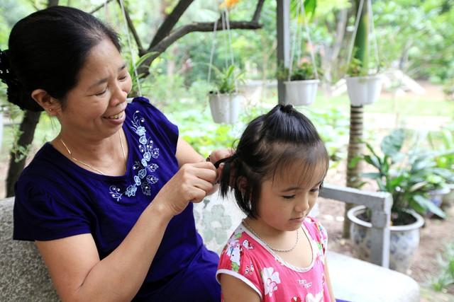 Mẹ Khuất Thị Lợi tết tóc cho con gái. Ảnh: Anh Tuấn