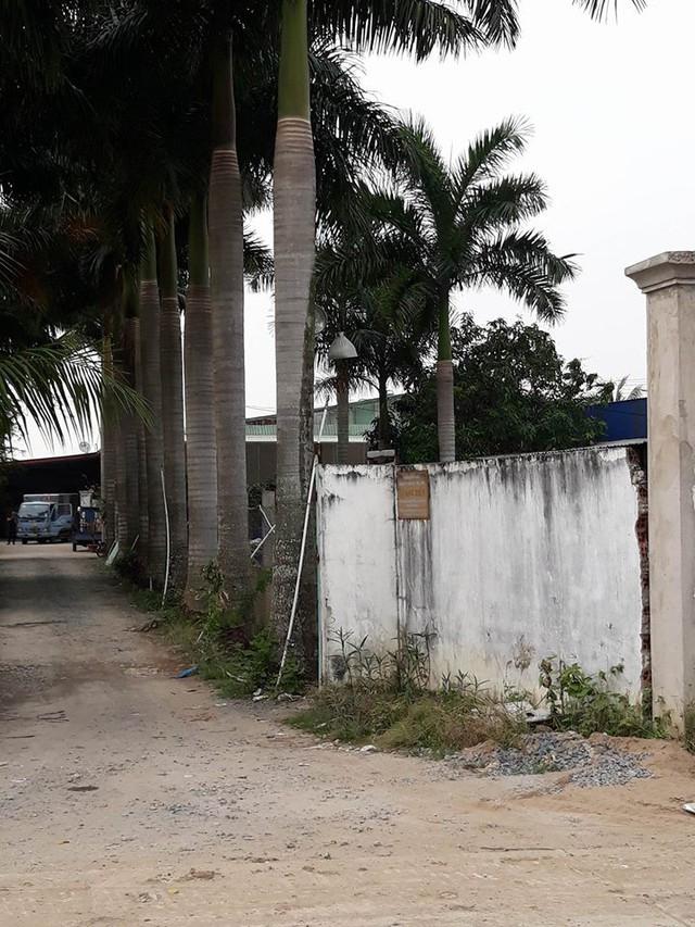 Biển hiệu công ty Quang Tiến nằm khiêm tốn trên bức tường rào phải lại gần mới nhìn rõ