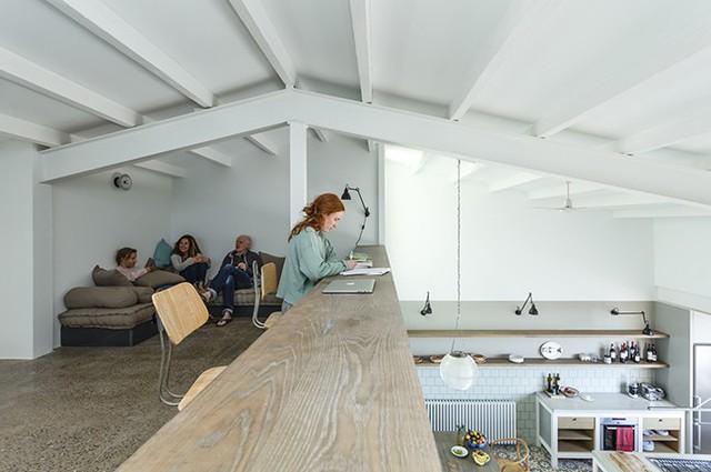 Tầng lửng áp mái được cải tạo thành một nơi thư giãn và phòng đọc lý tưởng.