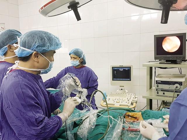 TS.BS Dương Văn Trung tiến hành lấy sỏi ra ngoài cho bệnh nhân. Ảnh: BSCC