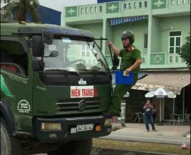 Chiến sĩ công an trật tự đu gương trên xe ô tô tải vi phạm. Ảnh: Cắt từ clip
