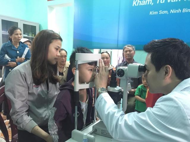 BS Đặng Xuân Nguyên - Giám đốc chuyên môn Bệnh viện Mắt Hà Nội 2 - khám mắt cho một bệnh nhi tại xã Kim Mỹ (Kim Sơn, Ninh Bình).