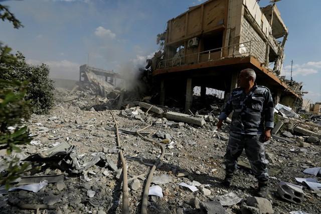 Một lính cứu hỏa đứng tại trung tâm nghiên cứu đã đổ nát tại Damascus. Ảnh: Reuters.