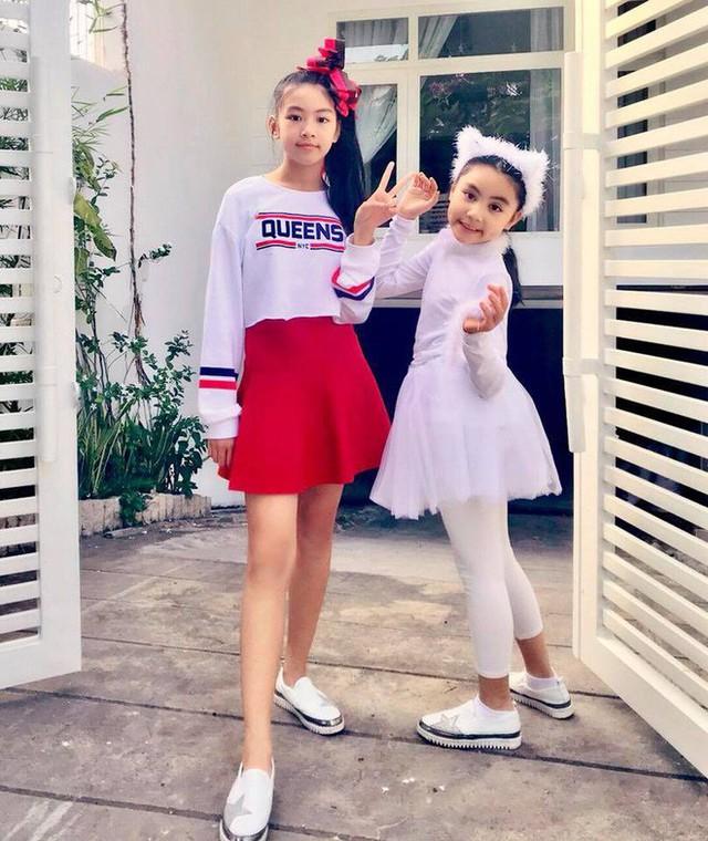 Hai cô con gái chụp ảnh trước cửa nhà.