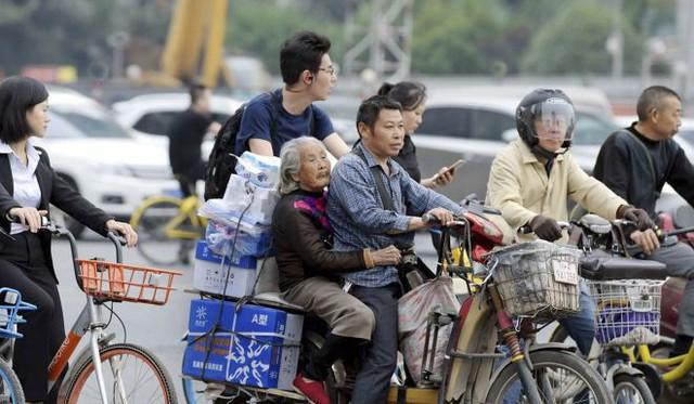 Giữ trọn phận làm con, người giao hàng chở mẹ già trên xe đạp suốt 7 năm, vừa làm việc lại tiện chăm sóc