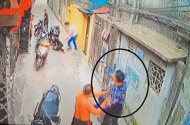 Nam thanh niên mặc áo hoa tay cầm súng bắn bà H. bị thương. Ảnh: Cắt từ clip