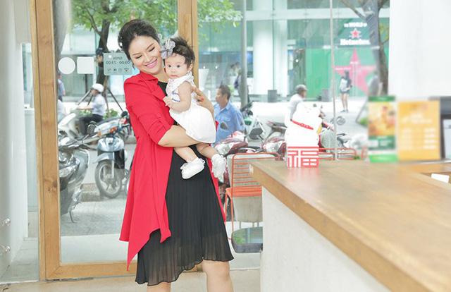 Nữ người mẫu bế con đi mua trà sữa ở trung tâm TP HCM.
