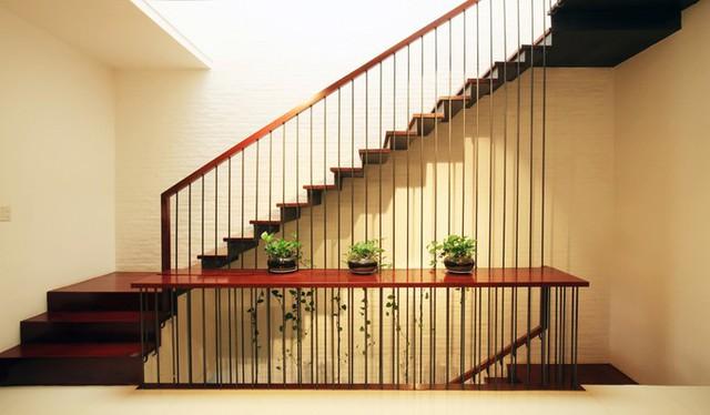 Cầu thang là sự kết hợp giữa sắt tấm và lan can sắt trơn với một vài bình dây leo trang trí tạo điểm nhấn nhẹ nhàng.