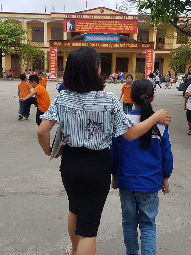 Phó hiệu trưởng trường Tiểu học An Đồng đang đi cùng bé Phương Anh vào trường.