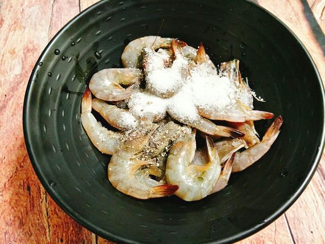 Cho tôm vào âu cùng với hạt nêm, tiêu, nước mắm, muối và đảo đều sau đó ướp tôm khoảng 15 phút cho ngấm gia vị. Hành khô và tỏi bạn băm nhuyễn, hành lá rửa sạch thái nhỏ cho ra đĩa.