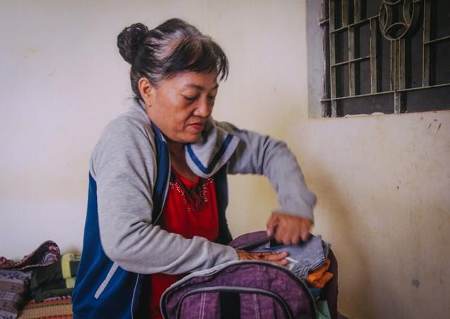 Bà Nhàn chuẩn bị quần áo để ra Huế đón con về Sài Gòn.