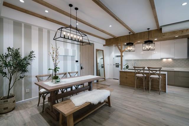 Phong cách đồng quê hiện đại được thể hiện rõ qua hệ thống đà gỗ giả, cột chống hình cây và các mảng tường gỗ được xử lý màu trắng và xám xanh.
