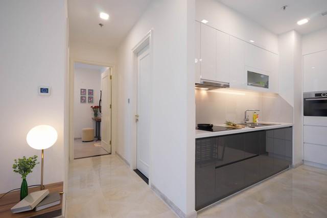 Khu bếp hình chữ L gọn gàng với tông màu đen trắng, thiết kế phẳng như các mảng tường.