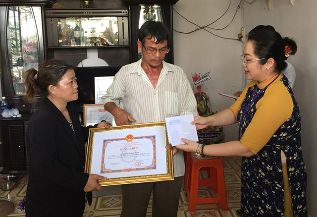Người thân hiệp sĩ Nam đón nhận bằng khen của UBND tỉnh Đồng Nai. Ảnh: N.A.
