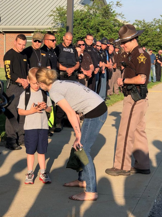 Dakota tự hào nâng niu phù hiệu cảnh sát của bố và được đồng nghiệp của ông cho biết bố mình anh hùng đến thế nào. Ảnh: CNN.