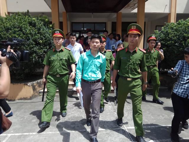 BS Hoàng Công Lương (giữa) rời khỏi phòng xử án trưa 7/5.