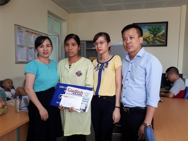 Đại diện chương trình Vòng tay nhân ái Báo Gia đình và Xã hội (bên trái) cùng đại diện CLB tình nguyện Haesung Vina trao tiền cho gia đình chị Mai
