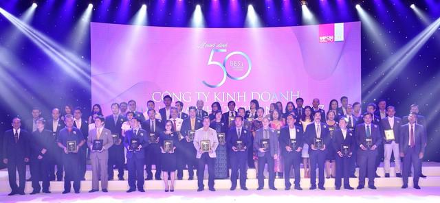 """Ông Nguyễn Quốc Khánh – Giám đốc Điều hành Vinamilk cùng các đại diện công ty được xếp hạng """"Top 50 công ty kinh doanh hiệu quả nhất Việt Nam"""" trên sân khấu sự kiện."""
