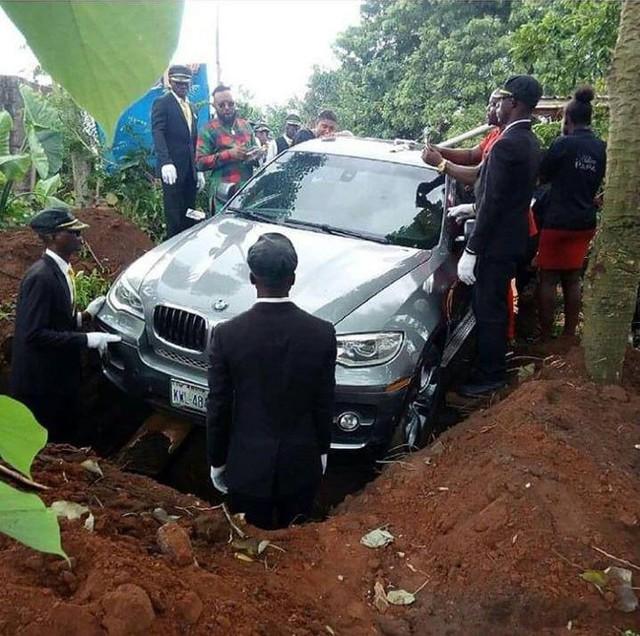 Chiếc BMW màu bạc mới tinh, chứa thi thể người bố bên trong, được hạ xuống huyệt. Ảnh: JAMIE PYATT.