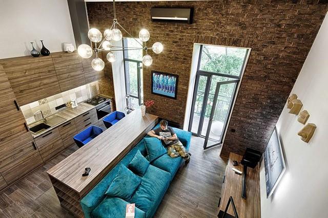 Chủ nhà chỉ sống một mình nên người thiết kế không bố trí bàn với các ghế xung quanh theo cách thông thường. Thay vào đó, một chiếc bàn được đặt ngay sau sofa đủ cho 2-3 người ngồi. Đó cũng là chỗ phân cách phòng khách và bếp nấu.