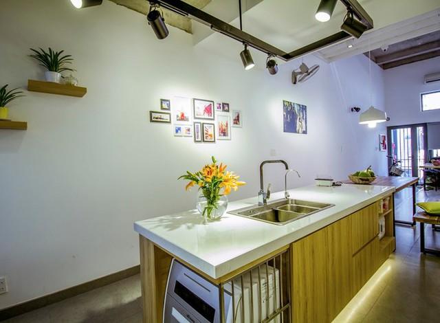 Khu vực bếp được tách biệt thành hai phần, chỗ nấu bố trí gọn gàng dưới cầu thang, tận dụng khoảng diện tích hay bỏ phí. Phần đảo bếp để sơ chế nằm giữa nhà, thuận tiện cho người thao tác.