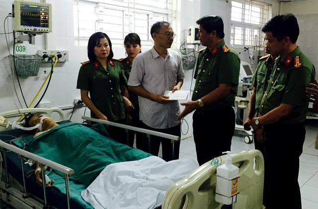 Đại tá Đinh Tiến Quân, Giám đốc Công an tỉnh Lào Cai thăm hỏi Trung úy Đoàn Văn Minh. Ảnh: TL