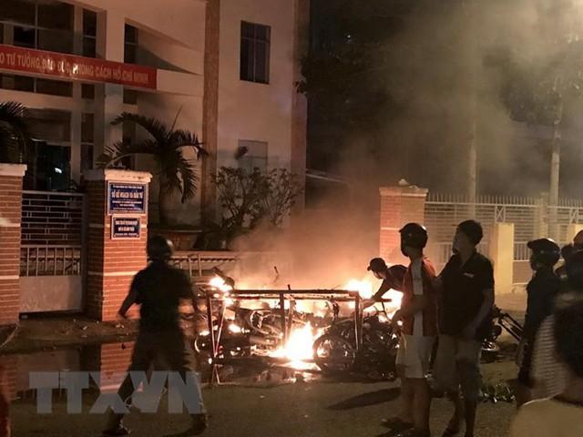 Một số đối tượng quá khích lôi xe máy từ trong Sở Kế hoạch và Đầu tư tỉnh Bình Thuận ra đốt phá. (Ảnh: Nguyễn Thanh/TTXVN)