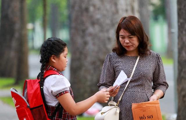 Tại điểm thi THCS Trần Văn Ơn, phụ huynh chở con đến trước giờ vào thi hơn cả tiếng, và không quên kiểm tra lại giấy tờ dự thi cho bé. Trong đó có nhiều thí sinh ở địa bàn xa trung tâm thành phố như quận 12, Bình Tân, huyện Hóc Môn, Bình Chánh.