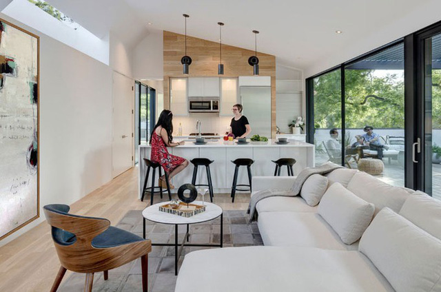 Phòng khách và khu bếp được kết nối thành một không gian mở nhìn ra phần hiên ngoài trời. Những mảng tường và sàn gỗ tạo cảm giác ấm áp cho ngôi nhà nhiều sắc trắng.