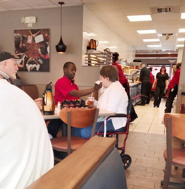 Nhân viên phục vụ ân cần đút thức ăn cho vị khách khuyết tật để chồng bà có thời gian dùng bữa.