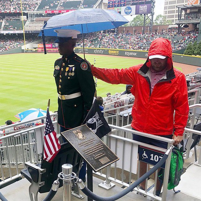 Một cổ động viện bóng chày đứng che ô cho viên sĩ quan tại trận đấu diễn ra ngay đúng ngày Tưởng niệm Liệt sĩ.