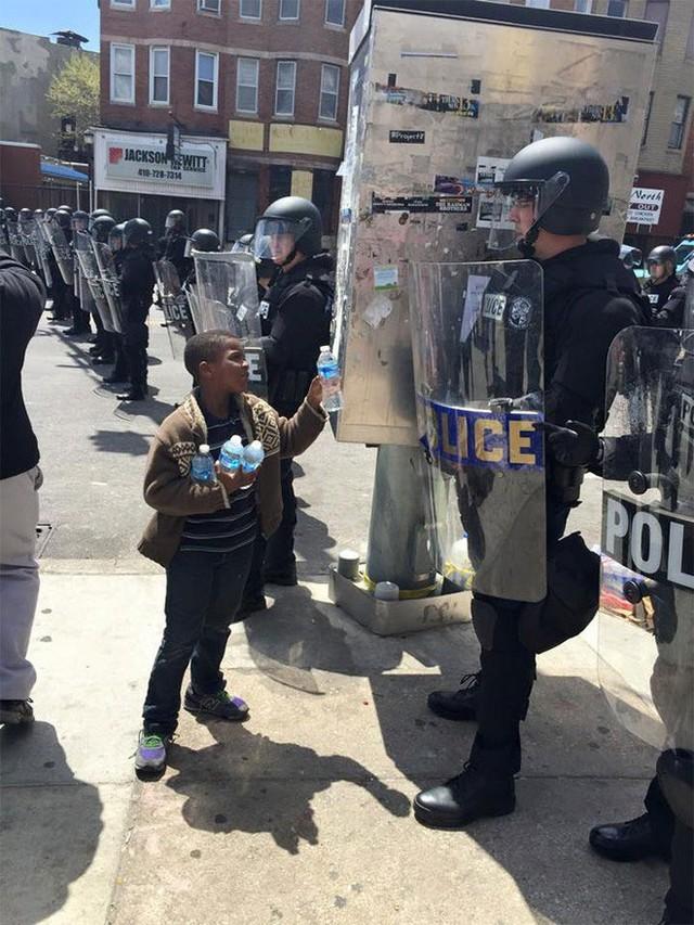 Cậu bé mời nước các chú cảnh sát đang phải vất vả làm nhiệm vụ giữa trời nắng nóng ở Baltimore.