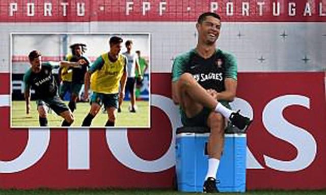 Ronaldo ngồi trên thùng nước đá vui cười nhìn đồng đội tập luyện.