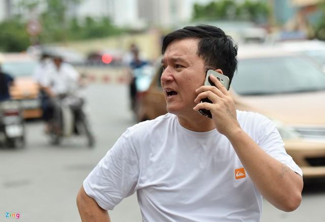 Một phụ huynh đứng ngoài cổng gọi điện cho con. Anh cho biết mình dặn con tắt điện thoại và để bên ngoài, đề phòng phí công bao năm đèn sách.