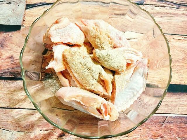 Cho cánh gà vào tô cùng với bột canh, hạt nêm, tiêu, bột tỏi rồi xóc đều, ướp cánh gà 30 phút cho ngấm gia vị.