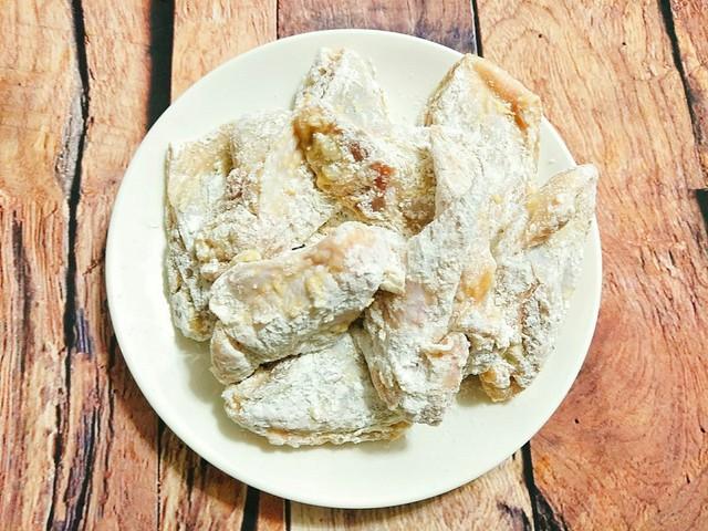 Cho bột nở, bột mì vào túi bóng và trộn đều sau đó cho cánh gà vào xóc đều để cánh gà bám một lớp bột bên ngoài.