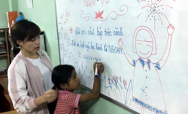 Cô Hiền đang kèm bé Linh tập viết trên bảng. Linh là học sinh chậm tiếp thu. Hiền cùng các bạn cố gắng trong nửa năm giúp bé Linh biết đọc và viết.
