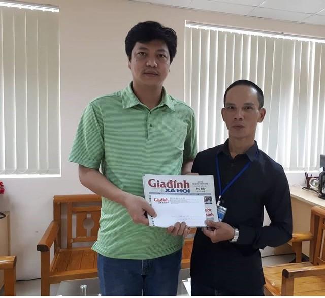 Đại diện chương trình Vòng tay nhân ái (Báo Gia đình và xã hội) trao tiền cho bố bé Dương. Ảnh PT