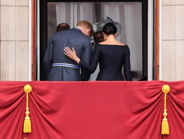 Nữ công tước xứ Sussex đặt tay lên lưng chồng khi rút lui khỏi ban công sau khi màn trình diễn kết thúc. Ảnh: PA, Andrew Parson, Rex Feature