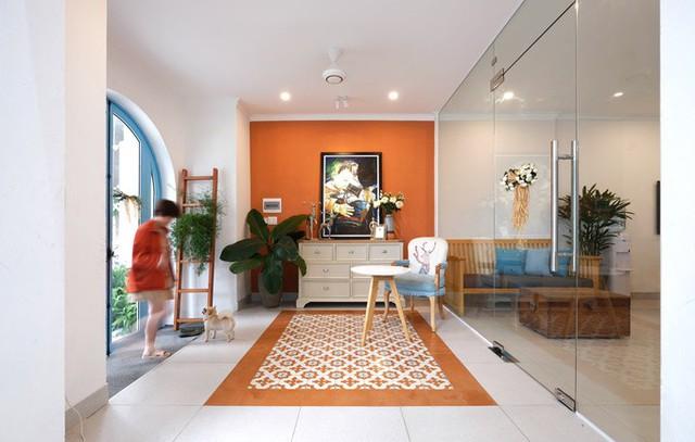 Ngoài sắc trắng-xanh, người thiết kế còn lựa chọn thêm màu cam kết hợp với cây cảnh, gỗ tự nhiên tạo nên liên kết giữa các không gian.