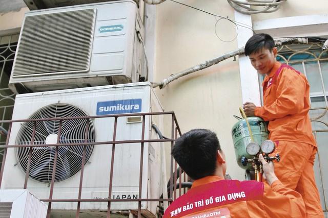 Để có mức thu nhập khủng, thợ sửa chữa điều hòa cũng đối diện với vô vàn nguy hiểm khi phải treo mình lơ lửng giữa không trung trong cái nắng chói chang. Ảnh: Kim Oanh