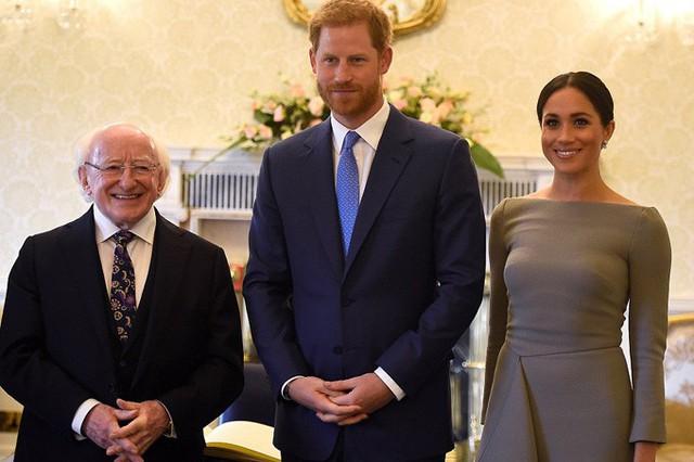 Harry và Meghan chụp ảnh cùng Tổng thống Higgins sau khi ký vào cuốn sách của khách mời tại dinh thự Aras an Uachtarain.