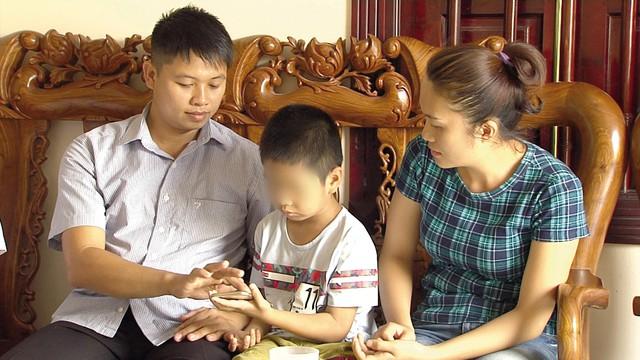 Bé Phùng Thanh H bên cạnh anh Sơn – chị Hiền, những người đã nuôi dưỡng bé từ khi lọt lòng tới nay. Ảnh: TL