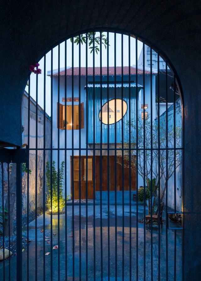 Thiết kế cổng nhà khá thú vị với chiếc cổng chữ U ngược và những chậu cây bê tông đóng vai trò hàng rào.