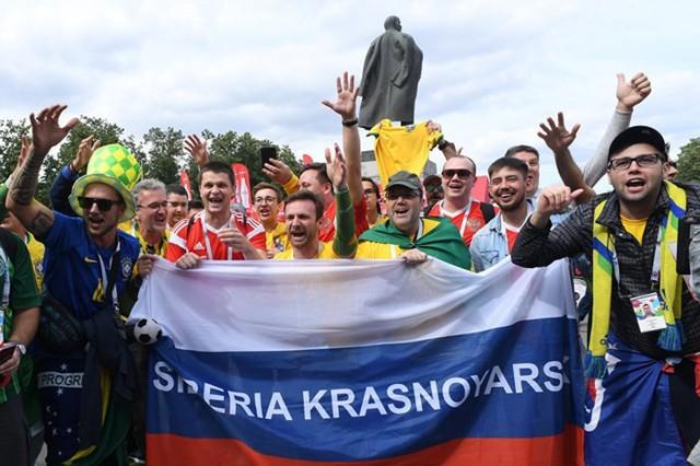 """Các cổ động viên của đội tuyển Nga chụp ảnh bên ngoài sân vận động Luzhniki trước giờ bóng lăn hôm 14/6. Ảnh: Sputnik.     Đại diện Sở Thể thao và Du lịch Moscow, ông Nikolai Gulyaev, cho biết trong thời gian một tháng diễn ra giải đấu, tổng số khách nước ngoài đến Nga du lịch lên đến 3 triệu người, tăng 60% so với cùng kỳ. Con số này được xem là sự tăng trưởng vượt bậc, nằm ngoài kỳ vọng ban đầu của giới chức Nga lẫn các công ty tư vấn thị trường.  Chủ các quán bia, rượu tại các con phố ở Nga cho hay, người hâm mộ bóng đá khắp các châu lục có xu hướng chi tiêu nhiều hơn, thậm chí gấp 2-3 lần so với khách du lịch tham quan ngày thường.  Điều này cho thấy doanh thu từ hoạt động du lịch rất có ý nghĩa với kinh tế Nga trong suốt thời gian diễn ra World Cup, bởi trung bình mỗi cổ động viên tiêu 5.000-8.000 USD cho đồ ăn, thức uống, khách sạn, giải trí và quà lưu niệm, Nga cũng đã có được một khoản thu khổng lồ.  Tuy nhiên, nhiều chuyên gia cho rằng sự bùng nổ trong ngành du lịch và bán lẻ tại Nga chỉ được thể hiện trong ngắn hạn, và khó để có thể duy trì trong thời gian tới.  Phó chủ tịch cơ quan đánh giá tín nhiệm quốc tế Moodys Christine Linde cho biết: """"Mặc dù World Cup kéo dài một tháng, so với quy mô kinh tế tổng thể của Nga, các biện pháp nhằm kích thích kinh tế vẫn còn tương đối yếu"""".  Đại diện Moody's cũng đánh giá doanh thu từ hoạt động du lịch, ngành hàng bán lẻ thực phẩm, giao thông vận tải ở Nga sẽ tăng, nhưng chỉ là một hiện tượng ngắn ngủi và không mang lại thay đổi đáng kể cho kinh tế nước này.     Dữ liệu về khách nước ngoài đến Nga qua các năm, theo Telegraph.      Với con số 15 tỷ USD mà McKinsey dự đoán, lợi ích tổng thể của World Cup tại Nga vượt qua các nước chủ nhà trước đó như Brazil, Nam Phi và Đức. Tuy nhiên, trên trang East Money, Ngân hàng Trung ương Nga ước tính World Cup sẽ đóng góp khoảng 0,1-0,2% GDP ở Nga trong 2 quý cuối năm 2018, đưa tốc độ tăng trưởng GDP trong nước đạt từ 1,5-2%.  Trong lịch sử các nước chủ nhà World Cup, chỉ Mỹ đăng """